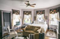 Easton Room - Bed surrounded by antique bay windows, seating area w/sleeper sofa