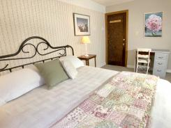 Flower room king bed, desk and entry.