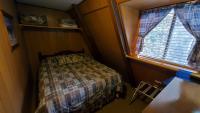 Queen bed in small bedroom in center of chalet.