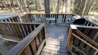 Deck at entrance to cabin with gas barbecue, table & chairs.